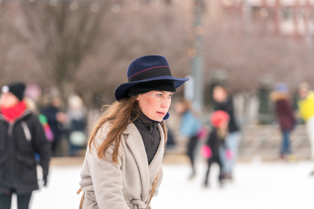 STOCKHOLM, SWEDEN - FEBRUARY 03, 2018: Side view portrait of a woman wearing hat and coat skating at a public ice skating rink outdoors in the city center of Stockholm february 03, 2018. Incidental people in the background. Editorial