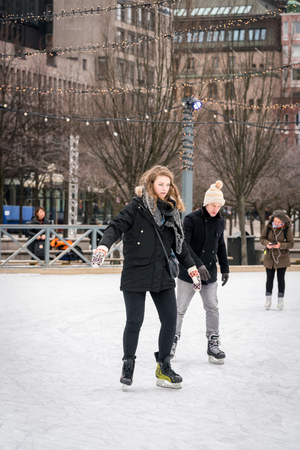 STOCKHOLM, SWEDEN - FEBRUARY 03, 2018: Front view of a young couple skating at a public ice skating rink outdoors in the city center of Stockholm february 03, 2018. Incidental people in the background. Stock Photo - 98937211