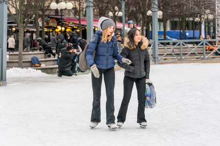 STOCKHOLM, SWEDEN - FEBRUARY 03, 2018: Front view of two girls skating at a public ice skating rink outdoors in the city center of Stockholm february 03, 2018. Incidental people in the background. Stock Photo - 98937214