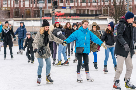 STOCKHOLM, SWEDEN - FEBRUARY 03, 2018: Front view of several happy young woman skating at a public ice skating rink outdoors in the city center of Stockholm february 03, 2018. Incidental people in the foreground and background. Stock Photo - 98937217