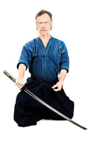 Caucasian male training Iaido, japanese sword sport. Sitting position.