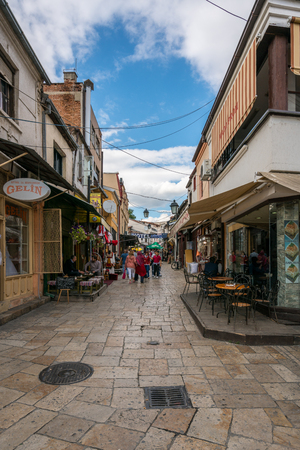 SKOPJE, MACEDONIA - SEPTEMBER 22, 2016: Narrow street in the old parts of Skopje September 22, 2016. Cafe, stores and restaurants on the side with people walking by on the street. Stock Photo - 98937359