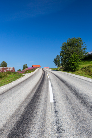 Straight gray asphalt road in country side with old buildings and blue sky. Stock Photo - 98955557