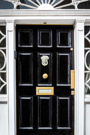 Traditional black entrance door with decorative letterbox in Dublin Ireland.