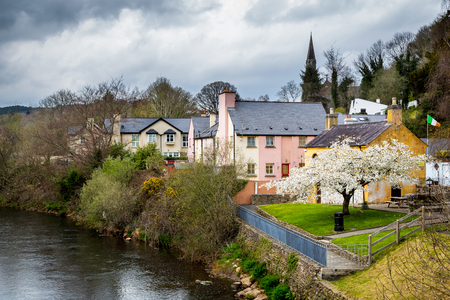 Idyllic Irish village with colorful houses by a river.