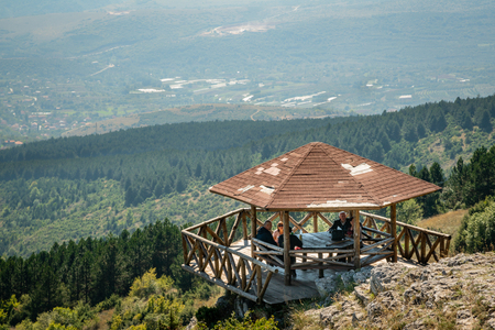 SKOPJE, MACEDONIA - SEPTEMBER 23, 2016: Mountain view of five people sitting at a picnic rest area overlooking the mountains in Skopje Macedonia September 23, 2016. Stock Photo - 98937913
