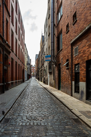 DUBLIN, IRELAND - APRIL 22, 2016: Narrow industrial street with cobblestone, signs and incidental people in the old parts of  Dublin April 22, 2016. Stock Photo - 98937916