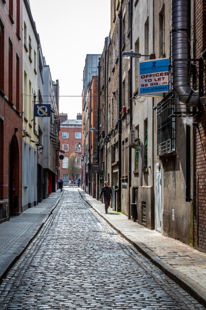 DUBLIN, IRELAND - APRIL 22, 2016: Narrow industrial street with cobblestone, signs and incidental people in the old parts of  Dublin April 22, 2016. Stock Photo - 98937917