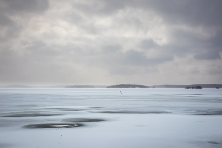 Beautiful winter seascape with hazy clouds and frozen sea. Stock Photo