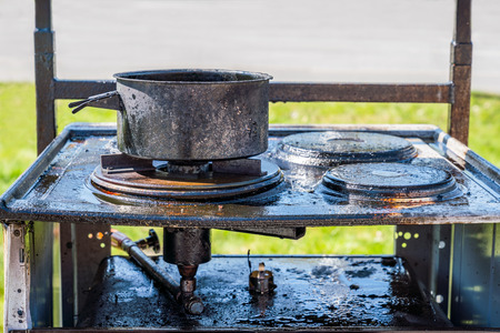 Close up of a burnt black gas stove covered with grease, a burnt pot on top. Stock Photo - 101148589