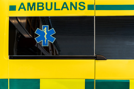 CLose up side view of a yellow and green Swedish ambulance vehicle. Editorial