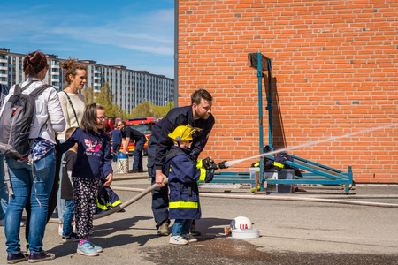 JARFALLA, SWEDEN - MAY 6, 2018: Side view of children and parents at a fire station trying a fire hose and sprays water, assisted by a fireman in Jarfalla May 6, 2018.