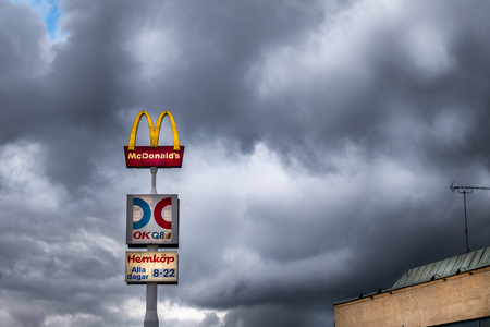 JARFALLA, SWEDEN - OCTOBER 29, 2014: Low angle view of a McDonald´s and gas station sign against a dramatic sky in Jarfalla October 29, 2014.