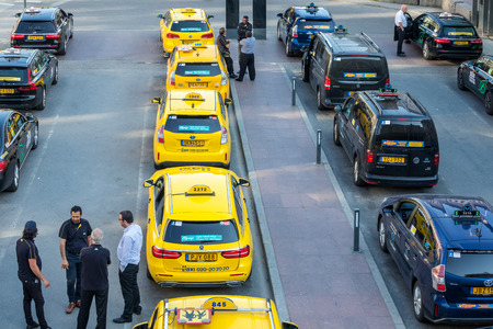 STOCKHOLM, SWEDEN - MAY 11, 2018: Horizontal high angle city view of many yellow and black taxis in line in the city of Stockholm May 11, 2018. Taxi drivers talking in the foreground.