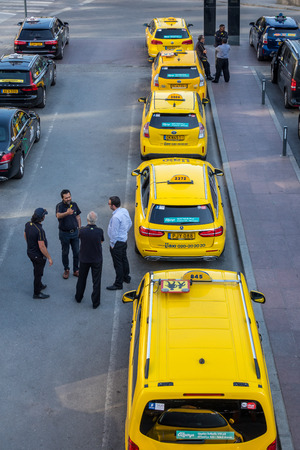 STOCKHOLM, SWEDEN - MAY 11, 2018: Vertical high angle city view of many yellow and black taxis in line in the city of Stockholm May 11, 2018. Taxi drivers talking in the foreground. Editorial