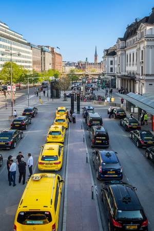 STOCKHOLM, SWEDEN - MAY 11, 2018: Vertical high wide angle city view of many yellow and black taxis in line in the city of Stockholm May 11, 2018. Taxi drivers talking in the foreground.