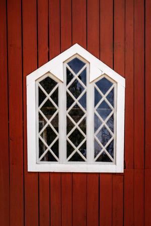 One white decorative traditional window with wooden frame on a red barn wall. Stock Photo