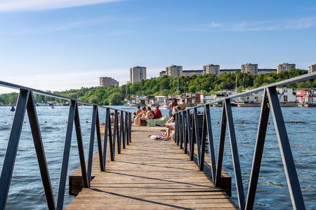 STOCKHOLM, SWEDEN - MAY 26, 2018: Summer city, people bathing and relaxing on a boardwalk with buildings and house boats in the background in Stockholm May 26, 2018.
