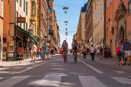 STOCKHOLM, SWEDEN - MAY 26, 2018: Low angle view of two men cycling and people walking on a city shopping street in Stockholm May 26, 2018.