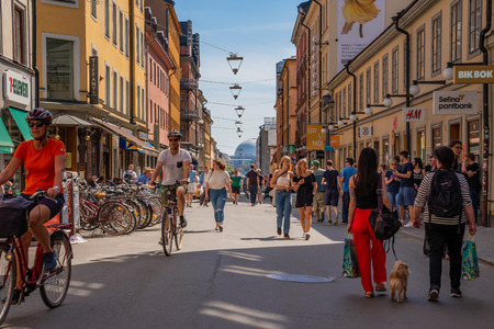 STOCKHOLM, SWEDEN - MAY 26, 2018: Front view of cyclists at a pedestrian city shopping street in Stockholm May 26, 2018. Incidental people walking by in the foreground and background. Editorial