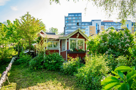 STOCKHOLM, SWEDEN - MAY 26, 2018: Front view of  a small traditional wooden cottage in the city with mordern office buildings in the background in Stockholm May 26, 2018. Editorial