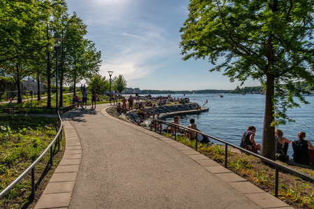 STOCKHOLM, SWEDEN - MAY 26, 2018: Beautiful summer city walkway by the water with people bathing and relaxing in Stockholm May 26, 2018.