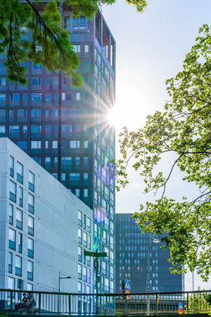 STOCKHOLM, SWEDEN - MAY 26, 2018: Low angle view of modern office building with trees and sun light flare in Stockholm May 26, 2018. Incidental people in the foreground. Editorial