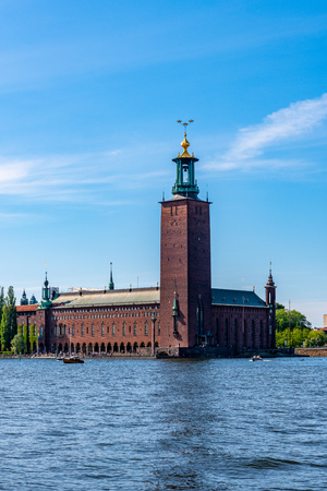 STOCKHOLM, SWEDEN - MAY 26, 2018: Beautiful summer front view of the famous brick building City Hall by the water in Stockholm Sweden May 26, 2018. Editorial