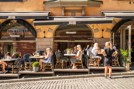 STOCKHOLM, SWEDEN - MAY 26, 2018:  Profile view of a outdoor restaurant with many guests having dinner and a female waitress in the foreground in Stockholm May 26, 2018. Editorial