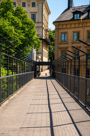 STOCKHOLM, SWEDEN - MAY 26, 2018: Perspective view of a pedestrian passage with steel fence  between buildings in Stockholm May 26, 2018. Incidental people in the background. Editorial