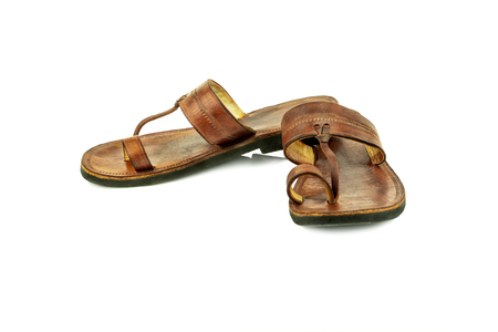 Front view of a pair of brown traditional indian leather sandals isolated on white background. Stock Photo