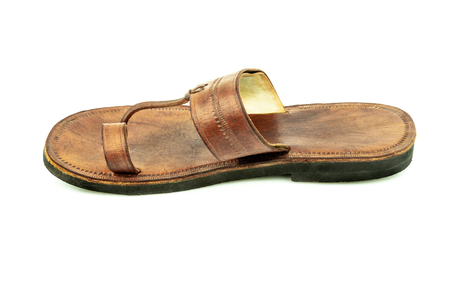 Profile view of one isolated indian traditional brown leather sandal.