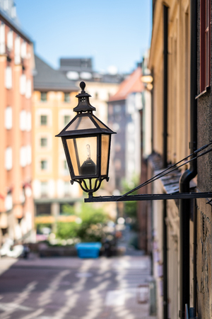 City view of a old vintage street light mounted on a exterior wall in Stockholm Sweden. Stock Photo