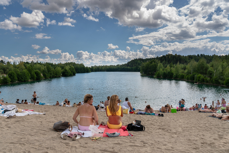 EKERO, SWEDEN - JULY 10, 2018: Back view of two young woman and many people sunbathing and having picnic on a beach with a lake, forest and blue sky with clouds in the background in Ekero Sweden July 10, 2018.