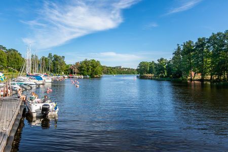 JARFALLA, SWEDEN - JUNE 9, 2018: Seascape front view of people on a moored motorboat at a boat refueling station with sailboats, water and trees in the background in Jarfalla June 9, 2018.