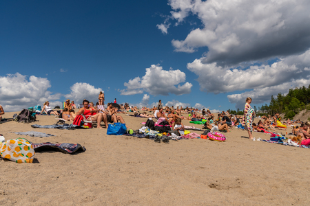 EKERO, SWEDEN - JULY 10, 2018: Low angle front view of many people sunbathing and having picnic on a beach with blue sky and clouds in the background in Ekero Sweden July 10, 2018. Editorial