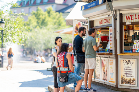 STOCKHOLM, SWEDEN - JULY 16, 2018: Selective focus side view of two woman and two men buying ice-cream at an outdoor ice-cream bar in a city square in Stockholm Sweden July 16, 2018. Incidental people in the background. Editorial