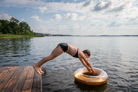 Side view of one young girl diving into water and svim ring from a jetty at a summer lake. Stock Photo