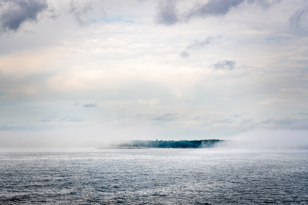 Beautiful nordic archipelago summer view  of a island surrounded by thick haze and fog at the horizon. Stock Photo