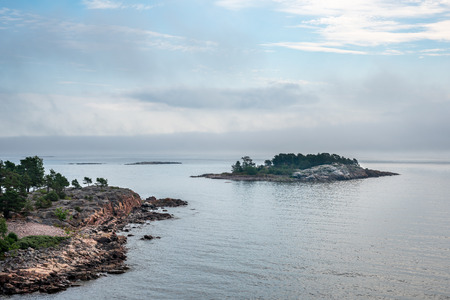Beautiful nordic archipelago summer view  of land and island against sea and hazy horizon.