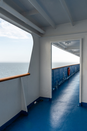 Perspective view of outdoor steel deck at a cruise ship with sea and horizon in the background. Vertical view. Stock Photo