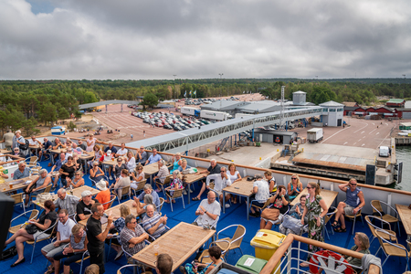 ALAND, FINLAND - JULY 31, 2018: Top view of many people sitting on deck outdoors at at cruise ship in Aland Finland july 31, 2018. Port with landscape in the background.