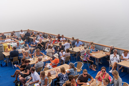 ALAND, FINLAND - JULY 31, 2018: Top view of many people sitting on deck outdoors at at cruise ship in Aland Finland july 31, 2018. Thick mist and fog in the background. Editorial