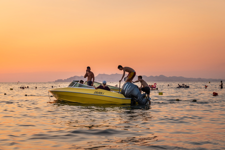 DURRES ALBANIA, AUGUST 5, 2018: Close sea view of orange and yellow sunset with people in a moored motorboat against the horizon in Durres Albania August 5, 2018. Incidental people bathing in the background. Editorial
