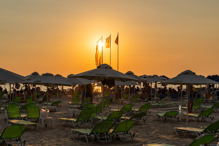 DURRES ALBANIA, AUGUST 5, 2018: Beautiful orange and yellow sunset view with people lying in sunchairs at a beach with sun umbrellas and flags in Durres Albania August 5, 2018. Editorial