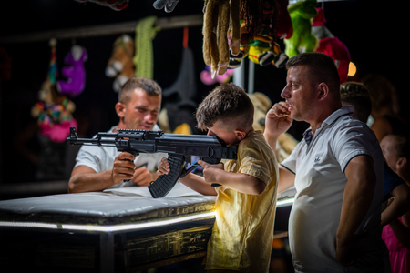 DURRES ALBANIA, AUGUST 5, 2018: Night side view of a young boy and father shooting with airsoft automatic weapon at a fair in Durres Albania August 5, 2018. Incidental people in the background.