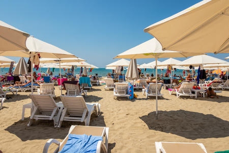 DURRES ALBANIA, AUGUST 5, 2018: Horizontal perspective view of people lying in sunchairs sunbathing at a beach in Durres Albania August 5, 2018. Ocean, blue sky and horizon in the background.