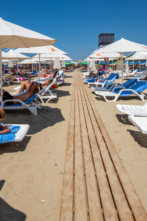 DURRES ALBANIA, AUGUST 5, 2018: Vertical perspective view of people lying in sunchairs sunbathing at a beach with a wooden boardwalk in Durres Albania August 5, 2018. Editorial