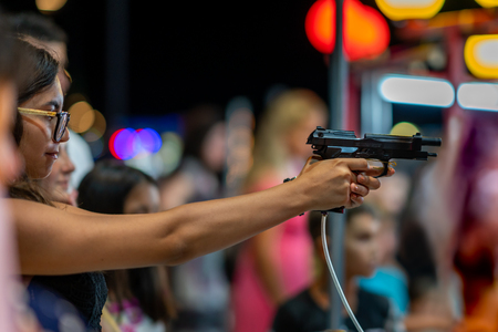 DURRES ALBANIA, AUGUST 5, 2018: Night side view of a young woman shooting with airsoft semi-automatic handgun at a fair in Durres Albania August 5, 2018. Incidental people in the background.