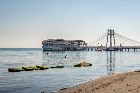 DURRES, ALBANIA - AUGUST 7, 2018: Outdoor side view of  a suspension pier with restaurant in Durres Albania August 7, 2018. Incidental people bathing in the foreground and people on the pier.